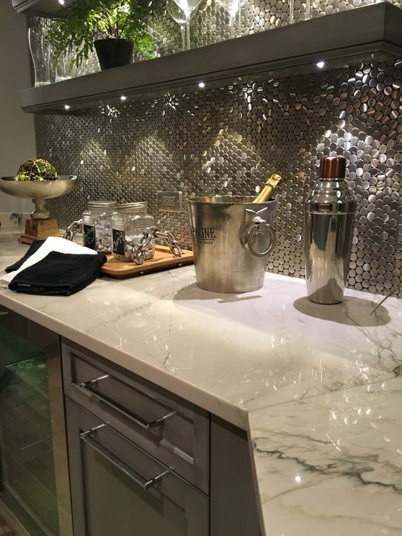 The gray cabinets help to pull the veining out of this quartzite and the shimmery backsplash helps. It's a bright look that's actually still toned down.
