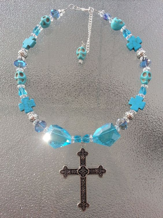 This is a aqua blue stone skull and glass beaded choker necklace with a cross pendant. It can be made in to any size. You can just message me with the size. It is made up of blue stone skull beads, blue glass beads, shiny silver beads, blue stone cross beads, blue cube beads, silver metal beads, blue ab beads and a silver metal cross pendant.