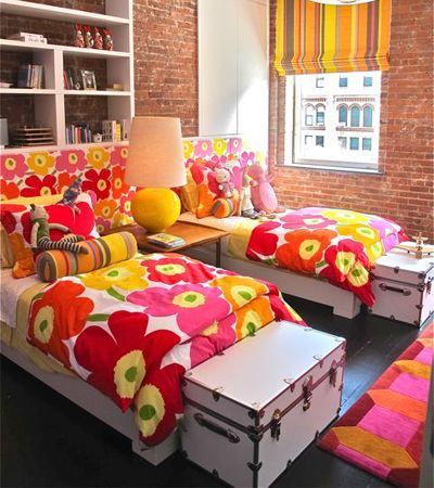 These bright and colourful Marimekko duvets are such a great contrast against the brick wall. The mix of patterns here is quite successful.: