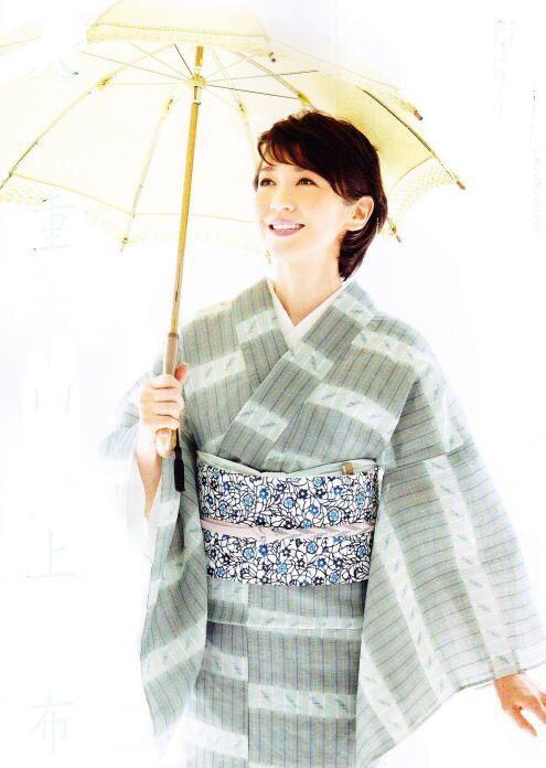 傘を差す賀来千賀子