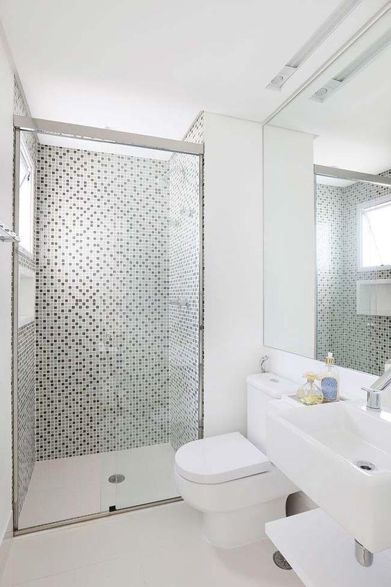 Pontos pretos quebram a monotonia branca do banheiro com pastilhas de vidro
