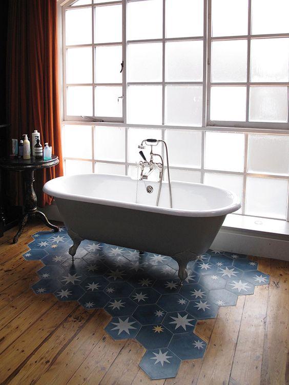 Patterned blue tiles under freestanding bath melting timber floor planks charles tashima for Blue patterned bathroom tiles