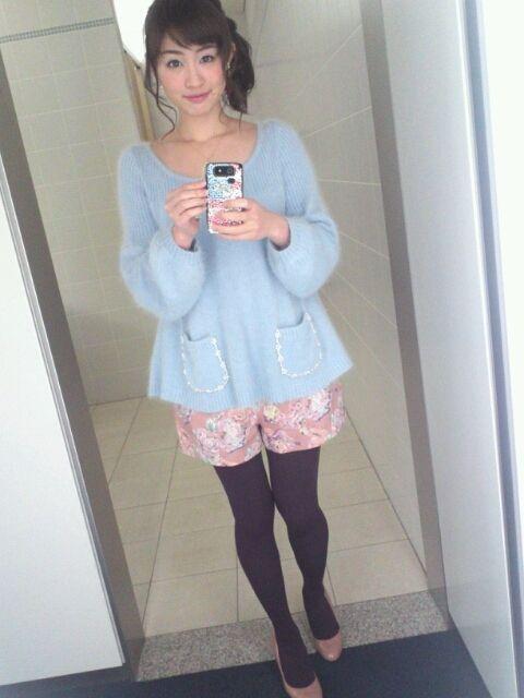 青色のトップスにピンク色の花がらのショートパンツ姿の新井恵理那