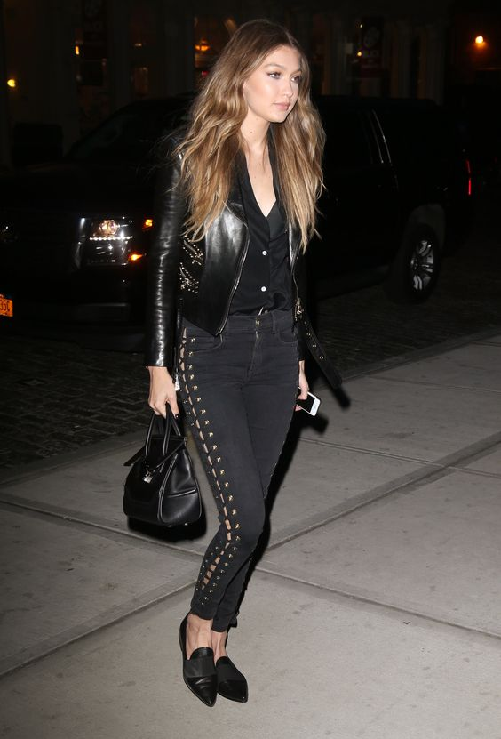 Gigi Hadid stepped out in NYC wearing a Versace leather jacket and black jeans with lace-up detailing down the side, accessorized with a Versace bag and Stuart Weitzman loafers.