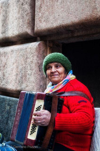 Suonatrice di fisarmonica in una strada di Genova by Germano Pozzati, via Flickr