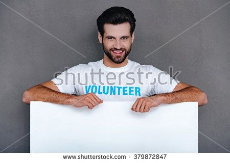 Please donate! Confident young man in volunteer t-shirt leaning to white board and looking at camera with smile while standing against grey background - stock photo