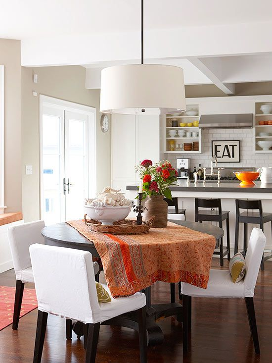 Connect an open floor plan by sprinkling similar fall-inspired hues throughout. A rich persimmon linen dresses this round dining table and links to orange, yellow, and red dishware showcased on open shelving in the nearby kitchen./