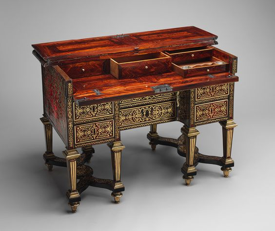 This desk, with a folding top that opens to reveal a small writing surface, is one of the few surviving pieces commissioned for Louis XIV's personal use. It was one of a pair intended for the king's petit cabinet, a small private room in the north wing of Versailles. The decoration on the top incorporates such royal symbols as the crown, the crossed L monogram, and the mask of Apollo, the sun god to whom Louis XIV likened himself. The four corners display openwork fleurs-de-lis, ...: