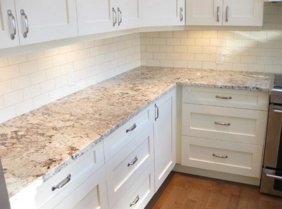 White Ice Granite With White Kitchen Cabinets And White Subway Tiles.