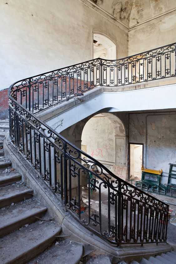 Magnificent main stone staircase with iron railings in a decaying French chateau. South of France Fixer Upper Château Gudanes. #southoffrance #frenchchateau #provence #frenchcountry #renovation