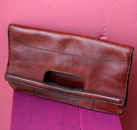 Vintage natural burgundy leather hand bag or clutch. Fantastic, good looking bag! It can be used as a small PC bag! There is some wear on the leather and inside the small pocket there is a hole. Vinyl lined. The bag measures 14 high and 13 wide. When folded as a clutch it measures 7 1/2 high and 13 wide.  Enjoy