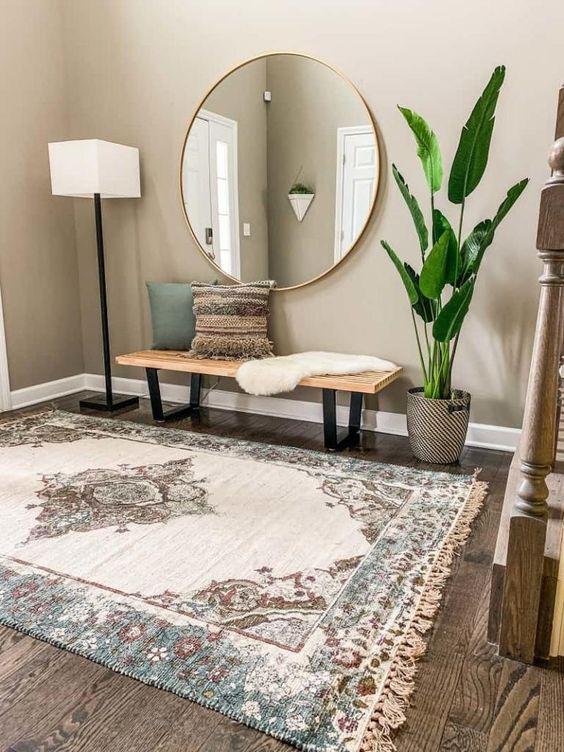 Recibidor con una alfombra grande y espejo redondo