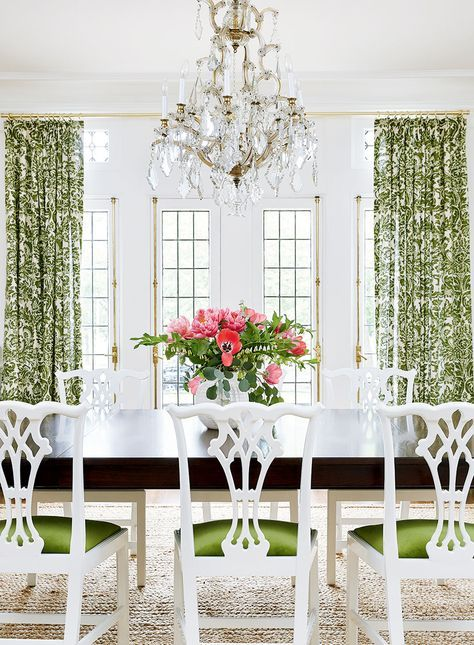 green and white dining room with seagrass rug and white Chippendale style dining chairs, crystal chandelier and white walls. Love the cremone bolts on the French doors too!