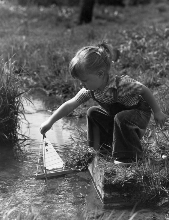 Circa 1945: Full-length image of a young girl crouching on the grassy banks of a stream, holding the mast of a toy sailboat in the water.:
