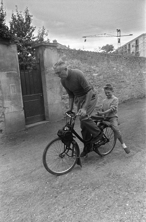 French actor and film director Jacques Tati and his son Pierre ride a Solex 330, a motorized bicycle, near his house: