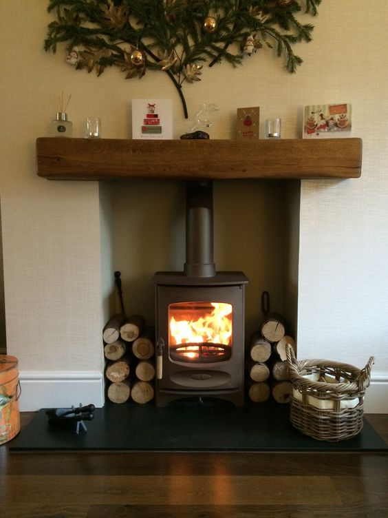 Charnwood C-Four in bronze, honed granite hearth, medium character medium colour oak fireplace beam. Christmas decorations.                                                                                                                                                     More