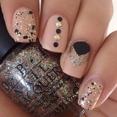 Nude nails with gold glitter and black accents.