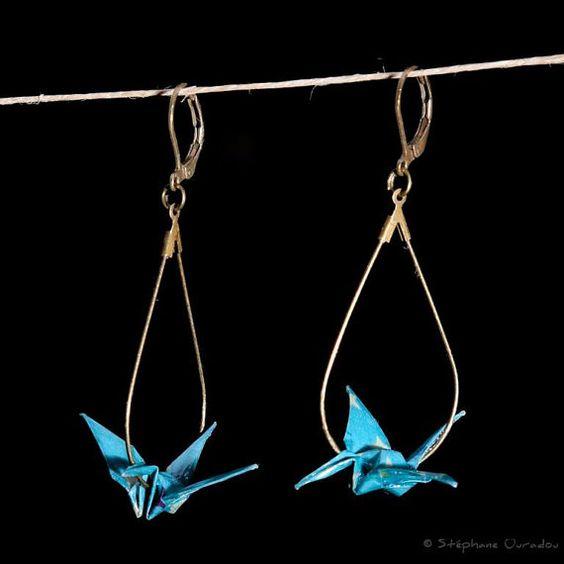 Boucles d'oreilles créoles en forme de goutte sur lesquelles une grue en origami s'est délicatement posée.  La grue est un animal porte-bonheur au Japon et symbolise la paix. La légende dit que quiconque pliera 1000 grues verra son vœu exaucé! Le papier japonais utilisé est de couleur bleue avec des motifs étoilés. Il est enduit de vernis le rendant à la fois brillant et résistant. Chaque boucle mesure 4,5 cm de hauteur. La grue a une envergure de 3,5 cm.  Photographie © Stéphane Ouradou