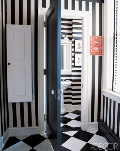 STRIPE WALLPAPER    The walls of the bathroom and adjacent laundry in a Chicago apartment are covered in Clarence House's Large Stripe wallpaper applied both vertically and horizontally; the checkerboard ceramic-tile floor is by American Olean.