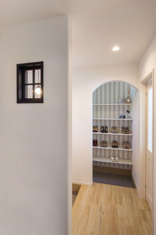 玄関ホール 玄関の壁にあしらった黒の小窓と アールの垂れ壁から