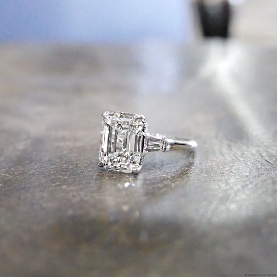 Three stones engagement ring set in Platinum with an Emerald cut diamond