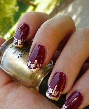 Uñas granate con flores doradas