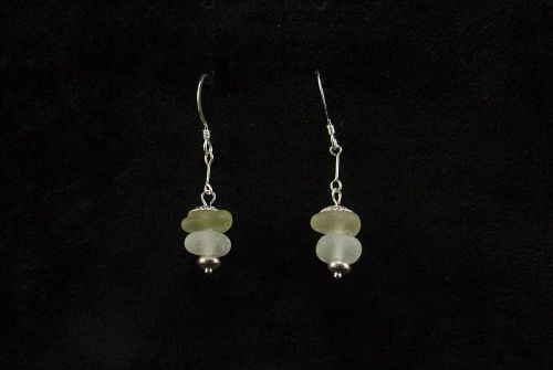 Here I have used Pale Green and Ice White sea glass and sterling silver to produce these stunning stacked earrings.Length from base of ear wire 24.43mm    Included a leaflet showing the process from collecting the sea glass to the finished piece of jewellery in my studio.   Sitting on a stunning frosted ice white base (The frosting is due to the hydration process while in the North sea for over 100 years.)