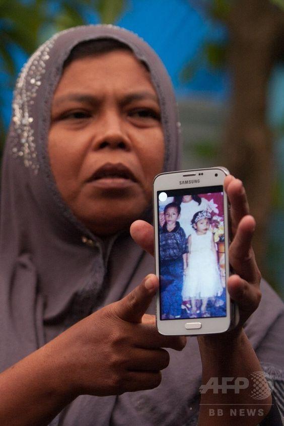 インドネシア・アチェ(Aceh)州ムラボ(Meulaboh)で、2002年の大津波で行方不明となっていた娘のラウダトゥル・ジャナ(Raudhatul Jannah)さんと息子の写真を見せるジャマリヤ(Jamaliah)さん(2014年8月7日撮影)。(c)AFP/CHAIDEER MAHYUDDIN ▼8Aug2014AFP|大津波で流された少女、10年ぶりに両親と再会 インドネシア http://www.afpbb.com/articles/-/3022630 #Meulaboh: