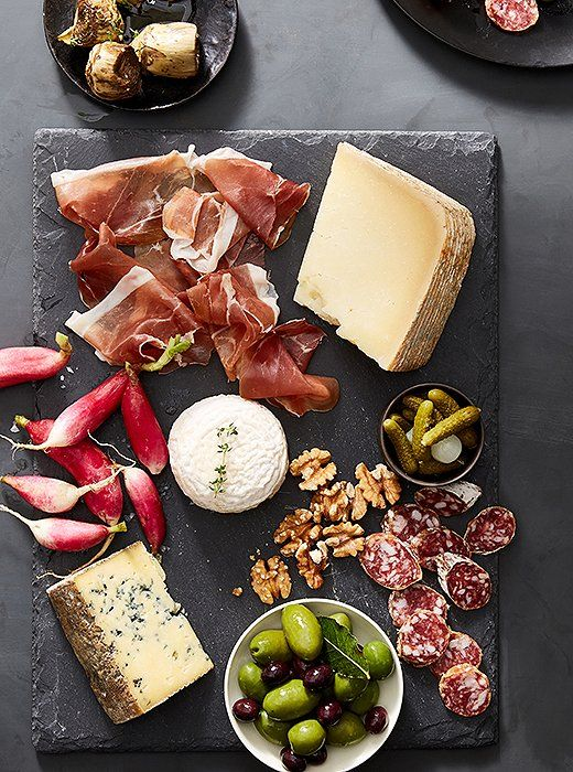 The dark slate board allows the beautiful colors of the radishes, olives, and meats to stand out.:
