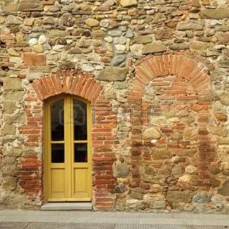 vecchi mattoni e muro di pietra con porta della casa toscana, Anghiari, Italia photo