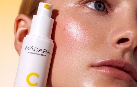 un primer plano de meio rostro con un bote de producto de vitamina C de Madara apoyado en la mejilla