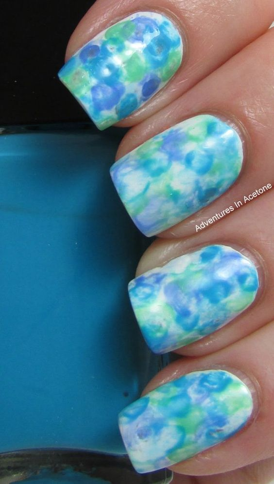 Hues of blue inspired watercolor nail art. Using white as your base color paint on various hues of blue on the top layer. The design looks calm and cool perfect for just about any occasion.