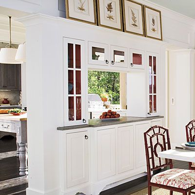 The cabinets between the dining room and kitchen open from both sides to let light pass through. Here designer Mallory Mathison added interest inside the double-sided cabinets with bold red paint.