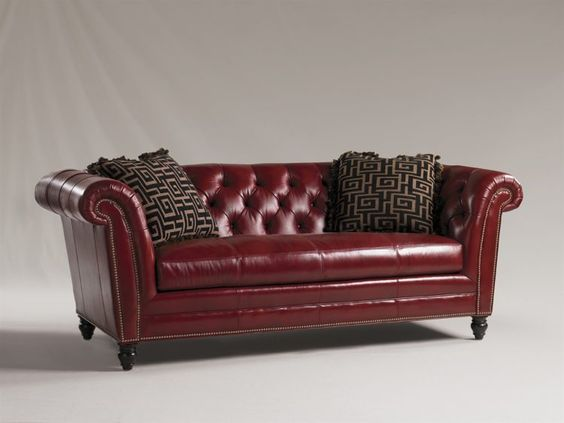 red leather couch with pillows