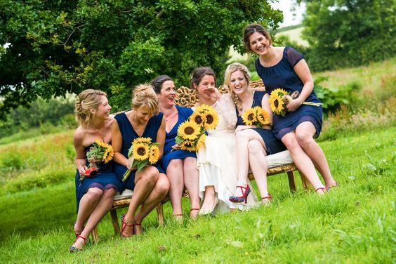 Bride and her bridesmaids on a sofa in the garden with sunflowers #funweddingphotos #bridesmaids #englishwedding #wedding #northdevonweddingphotography
