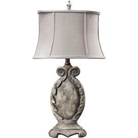 Cartouche-shaped table lamp with a cinched drum shade.   Product: Table lamp  Construction Material: Composite and fabric    Color: Gray and bone  Features:   Ornately designed base Flared shade    Accommodates: (1) 100 Watt medium base bulb - not included  Dimensions: 31 H x 16 W x 10 D