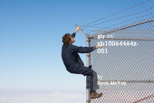 Man climbing chain link fence with barbed wire