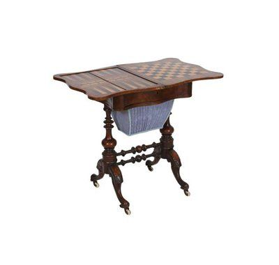 A Victorian burr walnut work and gaming table, the foldover top of serpentine outline, opening to reveal a marquetry playing surface, over a conforming frieze drawer with a sliding fabric lined well below, raised on baluster pillar ends continuing to leaf