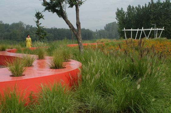 """Against a background of natural terrain and vegetation, is a """"red ribbon""""…"""