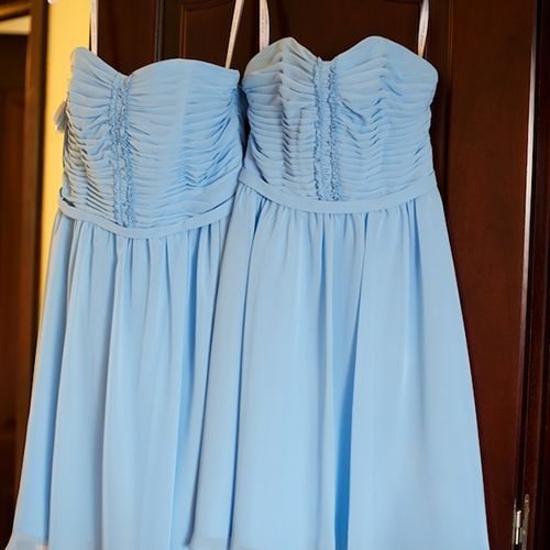 The bridesmaids hung up their light blue pleated dresses with sweetheart necklines.