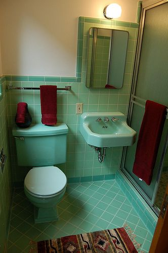 mint coloured bathroom suite in milton keynes accented with contrasting red bathroom accessories