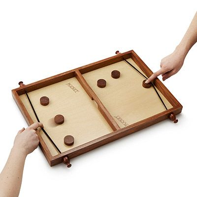 Two players, each with eight pucks, frantically flick their pieces through the opening at the board's center.