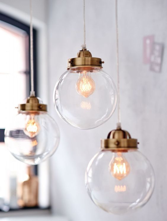 Eine Kugel aus klarem Glas und Metallelemente – so schlicht und schön kann eine Lampe sein. Tagsüber wirkt die Pendelleuchte wie eine Kunstinstallation, abends funkelt sie im Lichtschein und sorgt für eine stimmungsvolle Atmosphäre am Esstisch.