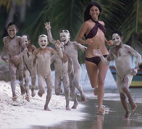 """""""It's tough to find a more unique/bizarre swimsuit photo than this shot of Tannia Rubiano running with a group of naked boys in the Dominican Republic. The image appeared in the 1971 SI Swimsuit issue with the caption: """"At Tiny Bayahibe Village, gangs of spirited skinny-dipping kids, after rolling in the fluffy white sand, race to the water."""""""