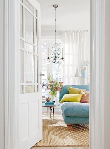 love the white white white room with colorful sofa and pillows.