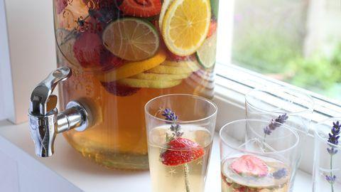 glasbehållare med dryck med frukt och bär i, på fönsterbräda, några glas med dryck i.