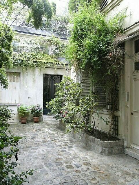 French courtyard with lush plants and shutters. European Farmhouse and French Country Decorating Style Photos. #french #courtyard #europeanfarmhouse
