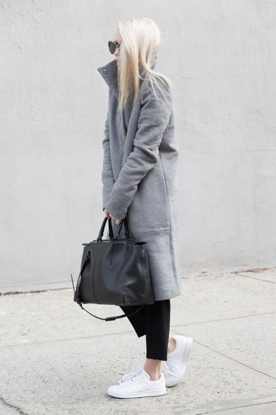 Figtny is wearing a grey funnel neck coat from Oak + Fort, black trousers from Aritzia and white Adidas:
