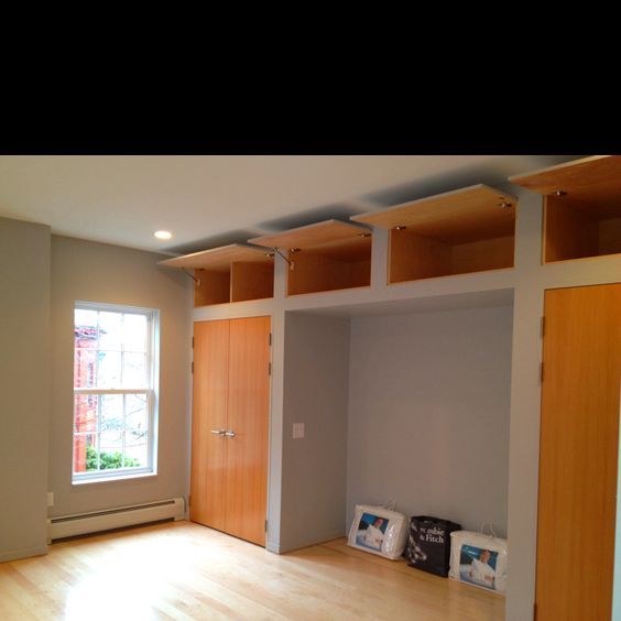 Bedroom With Built In High Ceiling Storage And Alcove For