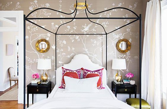 A black canopy bed boasts a gold halo held above a bed dressed in gray border…